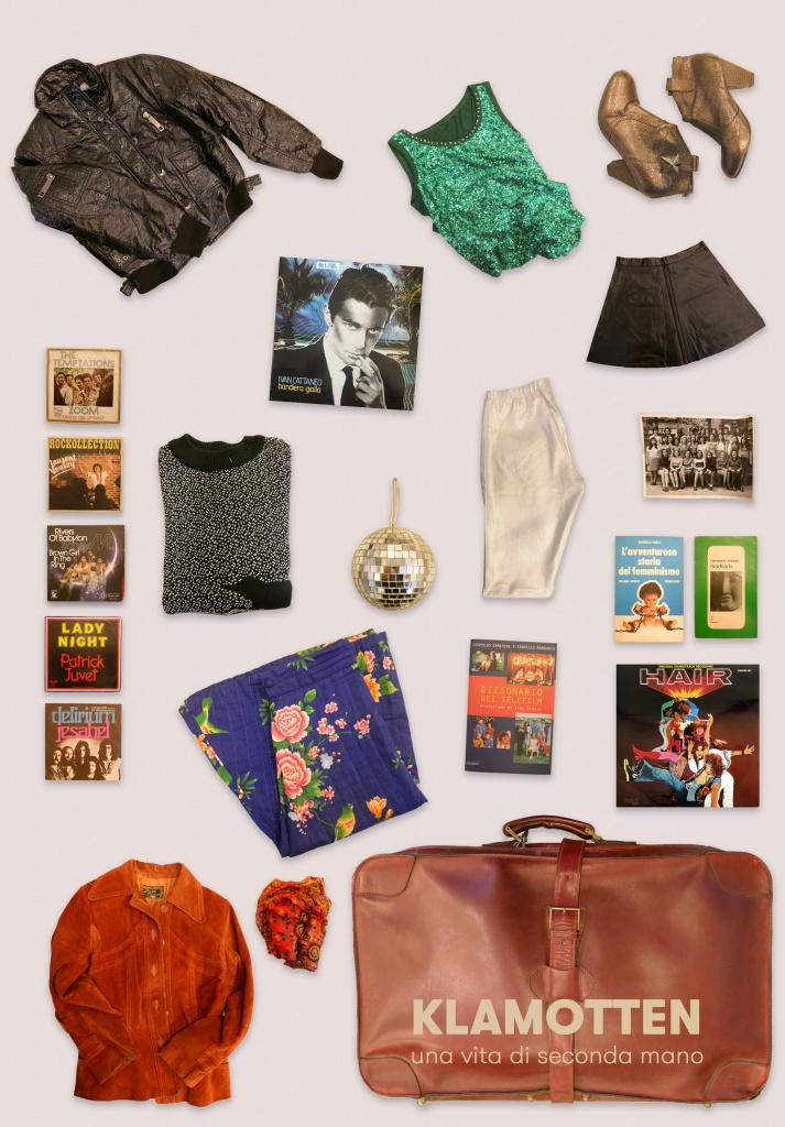 Klamotten - Una vita di seconda mano. Valigia con oggetti e vestiti secondhand.